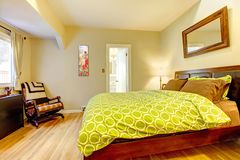 Modern green and beige bedroom with brown bed. Royalty Free Stock Image