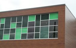 Modern green and dark glass panels embedded in a building Stock Photo