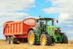 A modern green  john deere tractor. A modern green john deere tractor parked or carting on stubble with orange trailer full of crops in crop field Stock Images