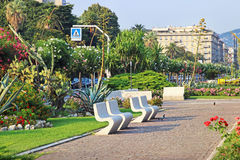Modern green park with stone benche. LA SPEZIA, ITALY - AUGUST 08, 2015: Modern green park with stone benches in La Spezia sea town in summer, Ligurian region Royalty Free Stock Photos