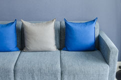Modern green sofa with blue and grey pillows Royalty Free Stock Images