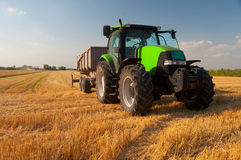 Modern green tractor on agricultural field during harvest Stock Photography
