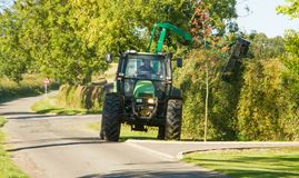 Modern green tractor cutting and maintaining  hedge Royalty Free Stock Photography