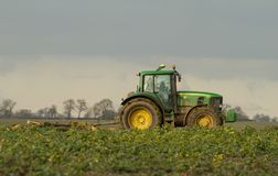 Modern green tractor hedge cutting last years crops Stock Images