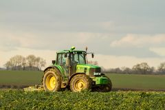 Modern green tractor hedge cutting last years crops Royalty Free Stock Images
