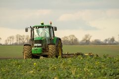 Modern green tractor hedge cutting last years crops Stock Photos