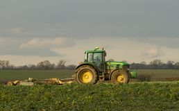 Modern green tractor hedge cutting last years crops Stock Image