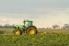Modern green tractor hedge cutting last years crops Royalty Free Stock Photos
