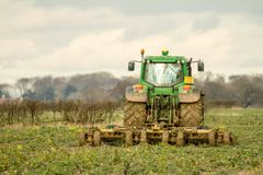 Modern green tractor hedge cutting last years crops royalty free stock image