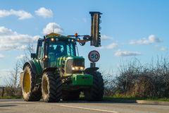 Modern green tractor hedge cutting on road Royalty Free Stock Photos