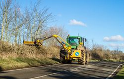 Modern green tractor hedge cutting on road Stock Photo