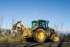Modern green tractor hedge cutting on road Royalty Free Stock Photography