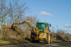 Modern green tractor hedge cutting on road Royalty Free Stock Images
