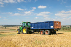Modern green tractor pulling a trailer in harvest field. Modern green john deere tractor pulling a blue trailer with crops in stubble field and big sky Royalty Free Stock Image