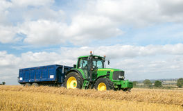 Modern green tractor pulling a trailer in harvest field. Modern green john deere tractor pulling a blue trailer with crops in stubble field and big sky Royalty Free Stock Photos