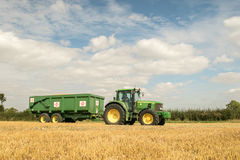 Modern green tractor pulling a trailer in harvest field. Modern green john deere tractor pulling a green trailer with crops in stubble field and big sky Stock Image