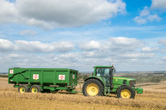 Modern green tractor pulling a trailer in harvest field. Modern green john deere tractor pulling a green trailer with crops in stubble field and big sky Stock Photo