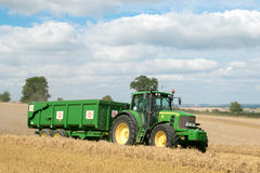 Modern green tractor pulling a trailer in harvest field. Modern green john deere tractor pulling a green trailer with crops in stubble field and big sky Stock Photos