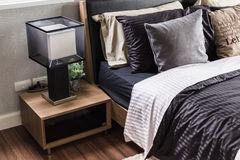 Modern grey bedroom with wooden nightstand and lamp Royalty Free Stock Photo