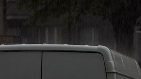 A modern grey car under the shower in a rainy day in summer. A dreamlike view of a modern grey car under the shower in a rainy day in summer. It happens in stock footage