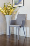 Modern grey chair with yellow flower in vase. At home Stock Photo