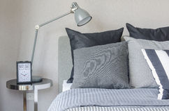 Modern grey lamp with alarm clock on side table in bedroom Royalty Free Stock Image