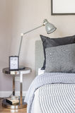 Modern grey lamp with alarm clock on side table in bedroom Royalty Free Stock Images