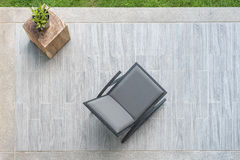 Modern grey leather chair with vase of plant on terrace Stock Image