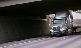 Modern grey semi truck under bridge on interstate highway Stock Photo