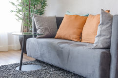 Modern grey sofa with orange pillows and round black table Stock Image
