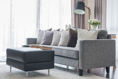 Modern grey sofa with pillows and black table in living room Stock Image
