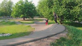 Modern groen park Twee jonge mensen die op een golvende speciale weg met een skateboard rijden stock footage