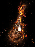 Modern guitar consumed in flames. Burning modern guitar consumed in fiery orange flames with flying sparks over a dark background in a conceptual image. 3d Stock Photos