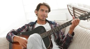 Modern guy with guitar sitting on sofa in living room. Royalty Free Stock Image