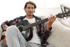 Modern guy with guitar sitting on sofa in living room. Royalty Free Stock Photography