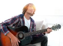 Modern guy playing guitar sitting on the couch. concept of a lifestyle. Photo with copy space Stock Images