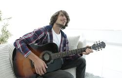 Modern guy playing guitar sitting on the couch. concept of a lifestyle. Photo with copy space Stock Image