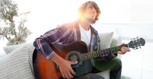 Modern guy playing guitar sitting on the couch. concept of a lifestyle. Photo with copy space Royalty Free Stock Photos