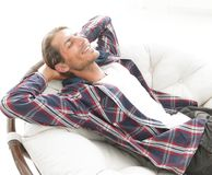 Modern guy is resting sitting in a large comfortable chair. side view. Stock Photos