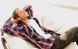 Modern guy is resting sitting in a large comfortable chair. side view. Royalty Free Stock Images