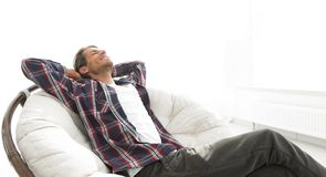Modern guy is resting sitting in a large comfortable chair. side view. Stock Images
