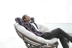 Modern guy is resting sitting in a large comfortable chair. side view. Royalty Free Stock Photography