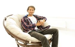 Modern guy sitting in a large comfortable chair. Stock Photography