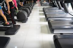 Modern gym interior with equipment. Fitness club with row of treadmills running part closeup.  stock photo