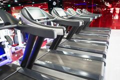Modern gym interior with equipment. Fitness club with row of treadmills running part closeup.  royalty free stock photo