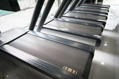 Modern gym interior with equipment. Fitness club with row of treadmills running part closeup.  royalty free stock photography