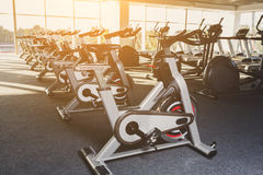 Modern gym interior with equipment, fitness exercise bikes. Modern gym interior with equipment. Fitness club with row of training exercise bikes, backlight Royalty Free Stock Photography
