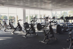 Modern gym interior with equipment, fitness exercise bikes Royalty Free Stock Image