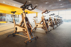 Modern gym interior with equipment, fitness exercise bikes. Modern gym interior with equipment. Fitness club with training exercise bikes, backlight stock images