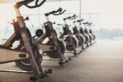 Modern gym interior with equipment, fitness exercise bikes. Modern gym interior with equipment. Row of training exercise bikes detail, backlight. Healthy Stock Photos